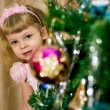 Girl looks out of New Year tree — Stock Photo #56175233