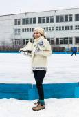 Smiling girl with fads on ice skating rink — Stock Photo
