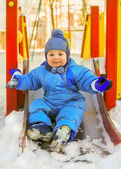 Happy kid on children playground in winter — Stock Photo