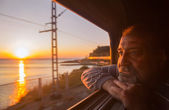 Man admires sea sunset from train — Stock Photo