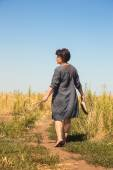Barefooted woman on path through field — Stock Photo