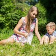 Mom pours little son milk from a jug on green forest glade — Stock Photo #81393760