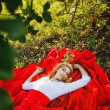 Woman in red skirt lying under the tree — Stock Photo #52066371
