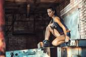 Sexy brutal woman sitting and holding handgun — Foto Stock