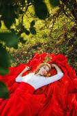 Woman in red skirt lying under the tree — Stock Photo