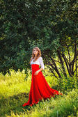 Woman in red skirt standing under the tree — Stock Photo