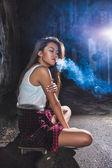 Asian woman sitting on skate and smoking — Stock Photo