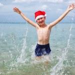 Happy boy wearing santa hat jumping in sea — Stock Photo #59005675