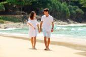 Lovely couple walking on beach together — Stock Photo