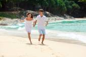 Happy couple running on tropical beach — Stock Photo