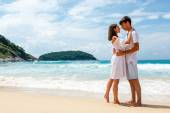 Young romantic couple on a beach, copy space left — Stock Photo