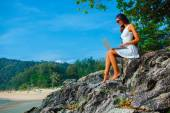 Woman sitting on the rock with laptop — Stock Photo