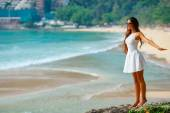 Beautiful woman in white dress at the rocks — Stock Photo