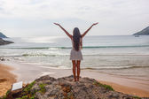 Woman stands on rocks in front of the ocean — Stock Photo