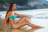 Tanned brunette sitting on the beach — Stock Photo