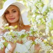 Blonde woman in a flowered garden — Stock Photo #75583253