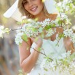 Blonde woman in a flowered garden — Stock Photo #75583269