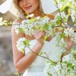 Blonde woman in a flowered garden — Stock Photo #75583291