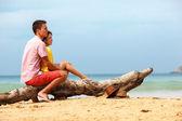 Lovely couple sitting on log — Stock Photo
