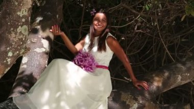 Bride in wedding dress sitting on tree — Stock Video