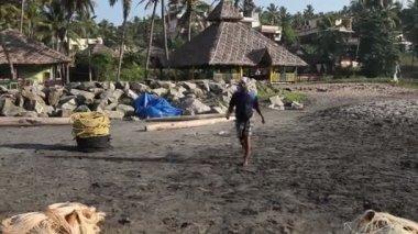 Fisherman walk on black sand — Stock Video