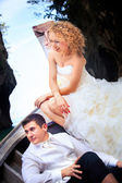 Blonde bride and handsome groom on boat — Stock Photo