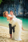 Bride and groom over sea water — Stock Photo