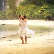 Bride and groom whirl and kiss on sand beach — Zdjęcie stockowe #65859857