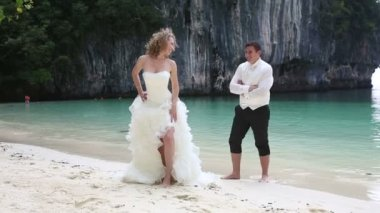 Bride in dress and handsome groom on island — Stock Video