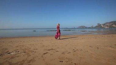 Blonde girl  walking along sea coast — Stock Video