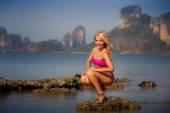 Blond tjej i baddräkt jämnar hår på sten — Stockfoto