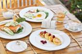 Yummy breakfast. Cheesecakes, Sandwich with Smoked Salmon, Fried Eggs With Bacon and Coffee — Stock Photo