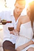 Tenderness couple with wine on sunset beach — Stock Photo