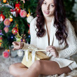 Happy young woman giving christmas present box — Stock Photo #54606053