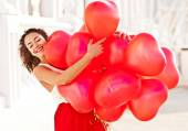 Young pretty woman holding red baloons-hearts. valentine day — Stock Photo