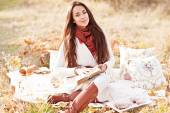 Young beautiful brunette drink tea and read book in the autumn park — Foto de Stock