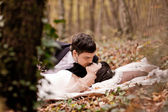 Wedding theme, the bride and groom are in the maple leaves on pillow in the forest — Stock Photo