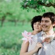 Young tenderness couple relax in blossoming garden — Stock Photo #62039665