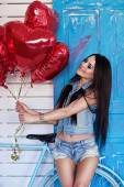 Beautiful brunette young woman in jeans  with a heart-shaped balloons near bicycle. Valentine's day. — Stock Photo