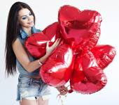Beautiful brunette young woman with a heart-shaped balloons. Valentine's day. — ストック写真