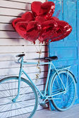 Blue bicycle with heart-shaped balloons. Valentine's day. — Stok fotoğraf
