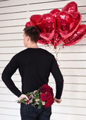 Man standing back with red heart balloons and roses. Surprise — Stock Photo