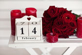 Red roses lay on the table near calendar  with the date of Febru — Stock Photo