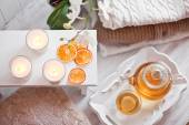 Tea-tray with hot grass drink, knitting clothes, dry oranges, ca — Stock Photo