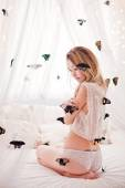 Beautiful young woman sitting on the white bed with butterfly. — Stockfoto