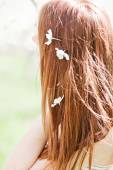 Small cherry flowers in woman's hair — Stock Photo