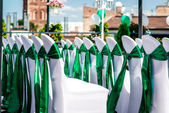 White wedding chairs with green ribbon outdoors — Stock Photo