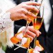 Hands of bride and groom with glasses of champagne — Stock Photo #67799015