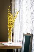 Spring yellow flowers in vase on a table near the window — Stock Photo
