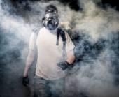Man in a gas mask walking through the smoke — Stock Photo
